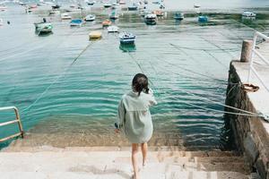 Frau rückwärts vor dem Meer mit vielen Booten an einem sonnigen Tag foto