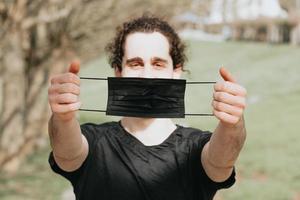 ein junger Mann mit einer schwarzen Gesichtsmaske foto