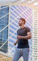 hübsche Männer, die Sportkleidung tragen und draußen in der Stadt laufen foto
