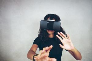 Eine schöne junge schwarze Frau mit lockigem Afro-Haar trägt Virtual Reality VR Headset und spielt Videospiele im Studio mit grauem Hintergrund foto