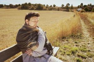 ein junger Mann mit einem warmen Schal, der in Ruhe die morgendliche Herbstsonne in einem gelben Feld mit der Hintergrundbeleuchtung vom blauen Himmel genießt foto