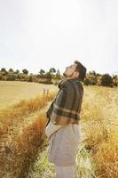 Seite eines Standes junger Mann, der in Ruhe die morgendliche Herbstsonne auf einem Weg eines gelben Feldes mit der Hintergrundbeleuchtung vom blauen Himmel genießt foto