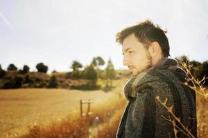 Seitenporträt eines jungen Mannes, der in Ruhe die morgendliche Herbstsonne auf einem Weg eines gelben Feldes mit der Hintergrundbeleuchtung vom blauen Himmel genießt foto