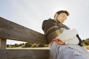 junger Mann, der die Morgenherbstsonne mit der Hintergrundbeleuchtung vom blauen Himmel schläft und genießt foto