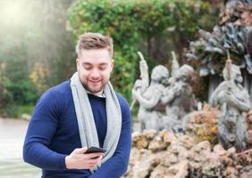 junger Mann, der in einem Park lächelt und sein Handy überprüft foto