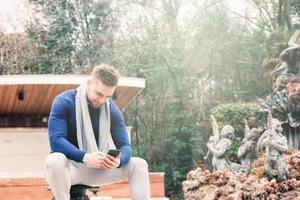 junger Mann, der im Brunnen eines Parks sitzt und sein Handy betrachtet foto