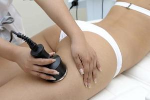 Kosmetologie-Nahaufnahme der Kosmetikerin, die Laser-Epilierungsbehandlung auf schönem weiblichem Körper tut, der Haare auf seidiger Haut entfernt foto