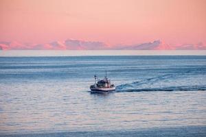 Fischerboot, das auf arktischem Meer kreuzt, um bei Sonnenuntergang im Winter zu fischen foto