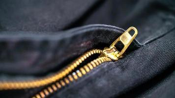 Nahaufnahme schwarzes Jeansmaterial und goldener Reißverschluss foto