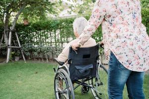 Helfen Sie asiatischen älteren oder älteren alten Dame Frau im elektrischen Rollstuhl und tragen Sie eine Gesichtsmaske zum Schutz der Sicherheitsinfektion covid 19 Coronavirus im Park foto