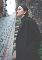 launisches, verträumtes Bild der modischen Person, die lächelt und in der schönen Umgebung in balat, Istanbul nach oben schaut foto