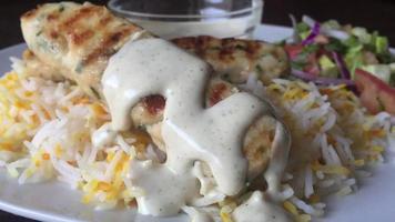 Nahaufnahme Fotografie von Hühnchen-Kebab mit weißer Sauce und gebratenem Reis serviert auf weißem Teller foto