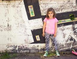 kleines Mädchen vor der Graffitiwand foto