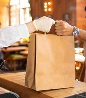 Arbeiter, der dem Kunden einen Beutel mit der Bestellung von Fertiggerichten gibt foto
