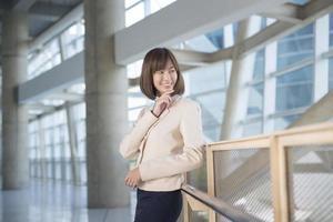 attraktive asiatische Geschäftsfrau, die außerhalb des Büros lächelt foto