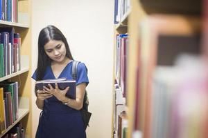 attraktives weibliches asiatisches Universitätsstudenten-Lesebuch in der Bibliothek foto