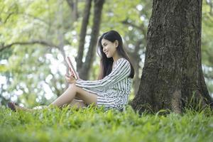 attraktive Frau, die ein Buch im Park liest foto