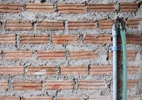 Wasserhahn auf Backsteinmauer mit Kopierraum foto