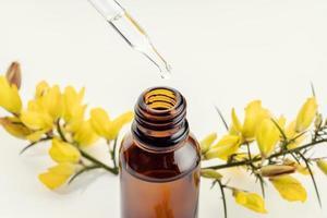 Nahaufnahme einer bernsteinfarbenen Pipettenflasche und eines gelben Blumenzweigs foto