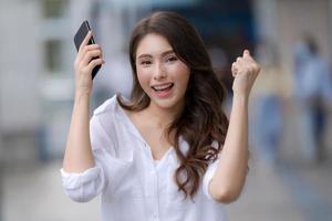 Porträt der jungen Frau mit Smiley-Gesicht unter Verwendung eines Telefons geht in einer Stadt foto