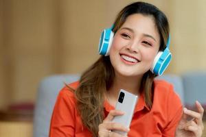 Porträt der jungen schönen Frau, die die Musik mit dem Smileygesicht genießt, das im kreativen Büro oder im Café sitzt foto