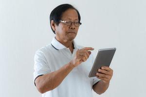 Porträt des asiatischen älteren Mannes unter Verwendung einer digitalen Tablette foto