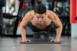 Sportmann Training macht Liegestütze Übung im Fitnessstudio foto