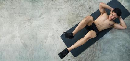 Sportlicher Mann, der Übung im Fitnessstudio trainiert foto