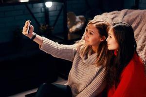Zwei süße Mädchen in Strickpullovern machen Selfies auf dem Smartphone foto