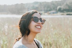 Frau mit Sonnenbrille, die zur Kamera lächelt, während auf dem Landhof foto