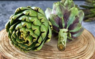Artischocken mit Gemüse auf einem Holzständer foto