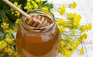 Glas Honig mit Rapsblüten auf einem hölzernen Hintergrund foto
