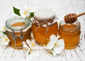 Honig mit Jasminblüten auf einem hölzernen Hintergrund foto