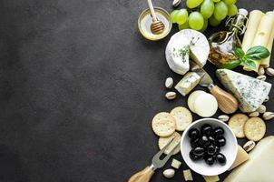 verschiedene Arten von Käse, Trauben, Honig und Snacks auf einem schwarzen Betonhintergrund foto