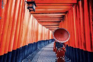 Mädchen mit traditioneller Kleidung in Fushimi Inari Taisha Schrein in Kyoto, Japan foto