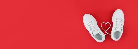 weiße Sportschuhe und Herzform aus Schnürsenkeln auf rotem Hintergrund einfache flache Lage mit Kopierraum foto