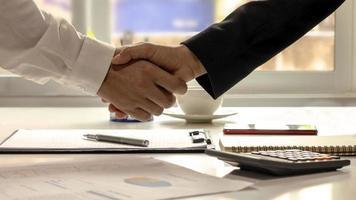 Die Geschäftsleute beendeten das Meeting und der glückliche Geschäftsmann Händedruck, nachdem der Vertrag geschlossen wurde, um ein Teamwork-Partner zu sein foto