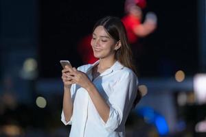 Outdoor-Porträt der jungen Frau mit lächelndem Gesicht mit einem Telefon in der Nacht foto