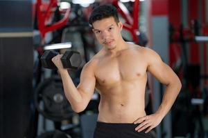 sportlicher Mann, der mit Hantel im Fitnessstudio trainiert foto