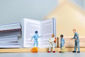 Miniaturmenschen, Schüler und Lehrer mit Schreibwaren, zurück zum Schulkonzept foto