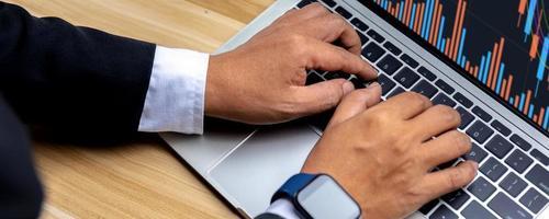 Nahaufnahme der Hand eines Geschäftsmanns, der die Daten des Finanzgeschäftsdiagramms auf dem Laptop betrachtet foto