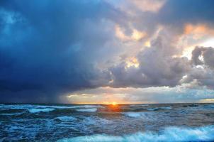 Küste Himmel Orange und Blautöne Wolken und Meereswellen schöne Natur heller Sonnenuntergang foto