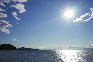Seelandschaft mit strahlendem Sonnenschein und einem Surfer unter einem roten Segel foto