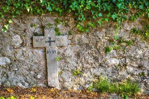 Kreuz auf Steinmauer foto