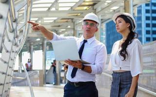 Ingenieure von Mann und Frau stehen mit ihren Laptops im Freien in den modernen Ingenieuren der Innenstadt, die aus Sicherheitsgründen weiße Schutzhelme tragen foto