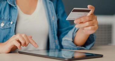 junge asiatische Dame mit Tablet-Online-Shopping-Produkt bestellen und Rechnungen mit Kreditkarte im Wohnzimmer bezahlen? foto