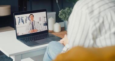 junge Asiatin mit Computer-Laptop über Krankheit in Videokonferenz mit Oberarzt Online-Beratung im Wohnzimmer im Haus sprechen foto