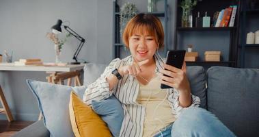 junge asiatische Dame mit Smartphone-Videoanruf sprechen mit der Familie auf dem Sofa im Wohnzimmer im Haus foto
