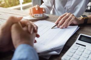 Immobilienmakler oder Bankkaufmann beschreibt dem Kunden die Kreditzinsen foto