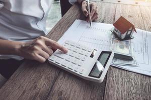 Kunde verwendet Stift und Taschenrechner, um das Hauskaufdarlehen zu berechnen foto